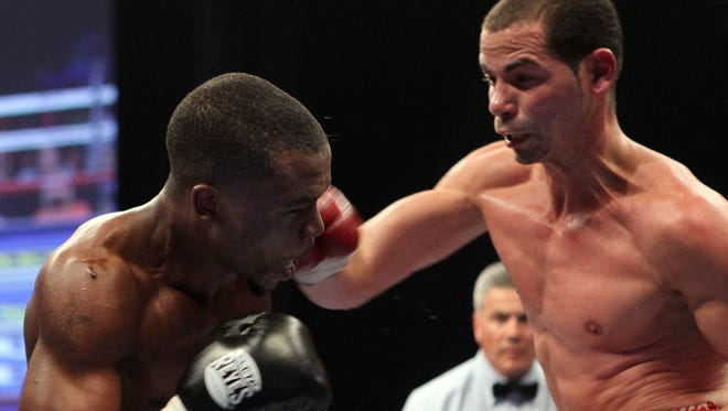 Richar Abril, right, lands a right to the jaw of Sharif Bogere Saturday night. Abril won a unanimous decision after a sluggish start to retain his WBA lightweight belt..