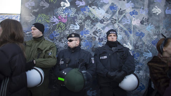 German police officers stand in front of a part of the Berlin Wall during a protest Sunday.