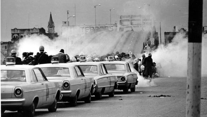 Tear gas fumes fill the air as state troopers break up a demonstration march in Selma, Ala., on what is known as Bloody Sunday, March 7, 1965.