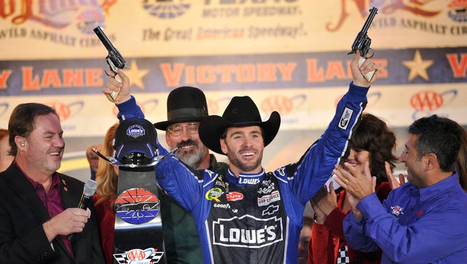Jimmie Johnson celebrates with a pair of six shooters as Texas Motor Speedway president Eddie Gossage, far left, looks on after Johnson won the Sprint Cup race in forth Worth on Nov 4, 2012.