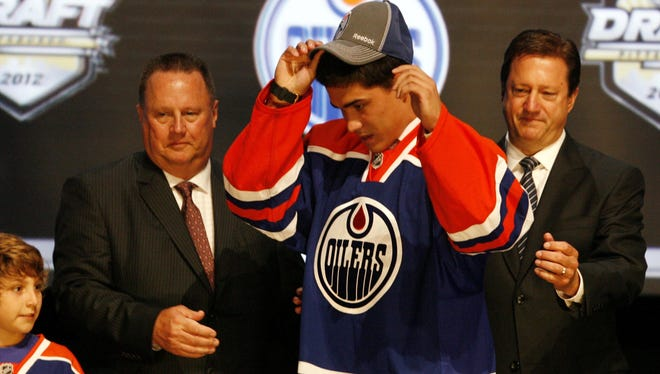 Nail Yakupov puts on an Edmonton Oilers cap and jersey after being selected as the No. 1 overall draft pick in June.