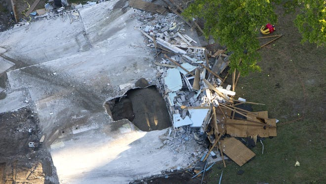 This Aerial photo shows the giant sinkhole at the home of Jeff Bush. Officials gave up hope of finding Bush alive and filled in the hole with crushed rock.