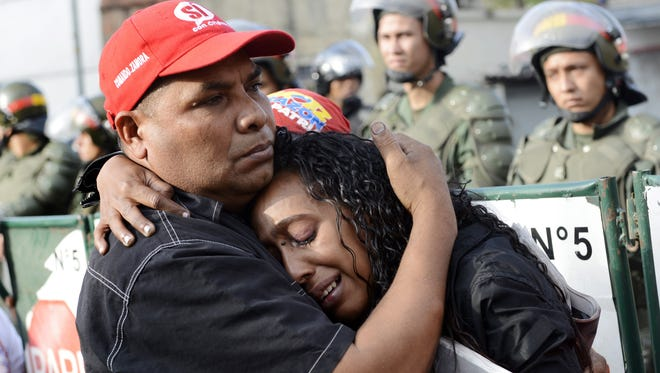 Supporters of Venezuelan President Hugo Chavez cry March 6 in front of the Military Hospital where he died a day earlier.