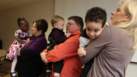April DeBoer, 40, holds her daughter Ryanne DeBoer-Rowse, 1, as her partner Jayne Rowse, 47, holds son Jacob DeBoer-Rowse, 2, and April's mother Wendy DeBoer, 62, holds Jayne's other son, Nolan DeBoer-Rowse, 2, after making a statement during a Jan. press conference.