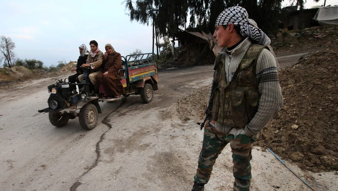 A Free Syrian Army fighter watches Syrian villagers pass a checkpoint Feb. 21 at the main entrance of Christian village of Yacobiyeh, Idlib province.
