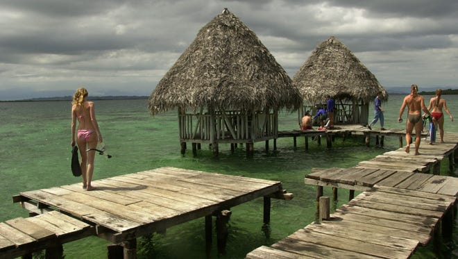 Tourists walk along the docks of the snorkeling area of Coral Key in Bocas del Toro, Panama. The archipelago also offers some of the Caribbean best breaks for surfing.