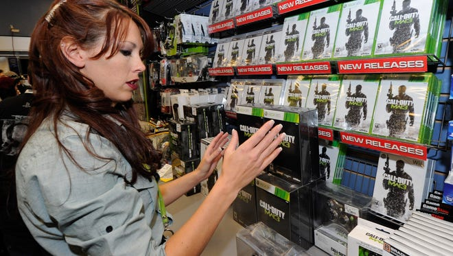 """GameStop employee Randi Taber stacks copies of """"Call of Duty: Modern Warfare 3"""" during a launch event for the highly anticipated video game at a GameStop store in Las Vegas."""