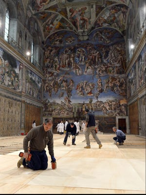Workers place floorboards on the ground inside the Sistine Chapel at the Vatican on Friday.