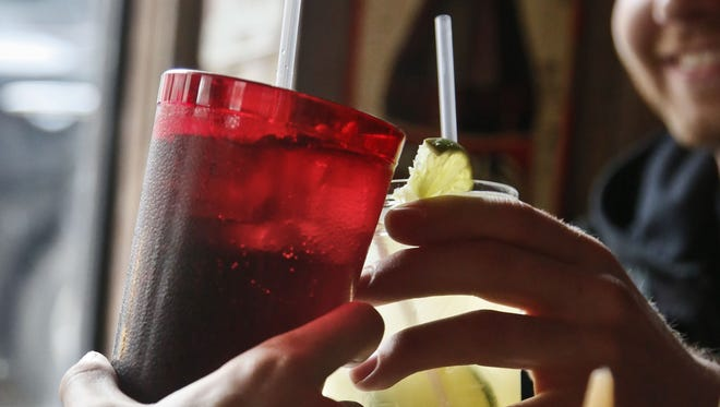 New Yorkers cheer with 24-ounce and 16-ounce beverages on Friday.