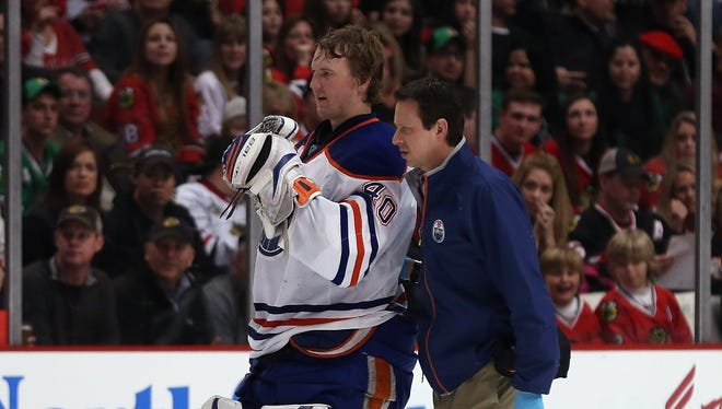 Devan Dubnyk of the Edmonton Oilers is escorted off the ice after being injured against the Chicago Blackhawks at the United Center on March 10, 2013 in Chicago, Illinois.