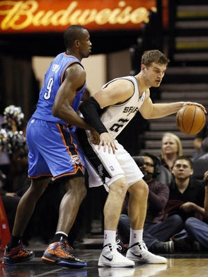 San Antonio Spurs forward Tiago Splitter (22) controls the ball as Oklahoma City Thunder forward Serge Ibaka (9)  defends during the second half at the AT&T Center.