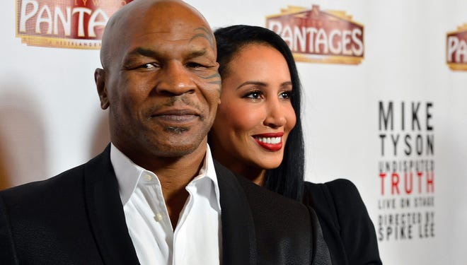 Mike Tyson's wife, Kiki Tyson, makes sure that he's the center of attention as they arrive at the opening Night Of 'Mike Tyson: Undisputed Truth' on March 8 in Hollywood.