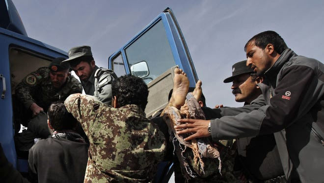 Afghan soldiers remove a dead passenger  after U.S. forces shot at an Afghan truck, killing two people and injuring another on the road between Kabul and Bagram on Monday.