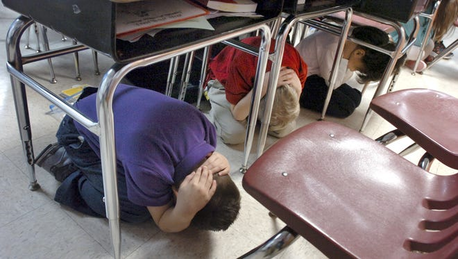 Students in Cheryl Logan's second-grade classroom at Kendall Elementary School take cover beneath their desks during the Great Central U.S. earthquake drill in Marion, Ind., on Thursday, Feb. 7, 2013.