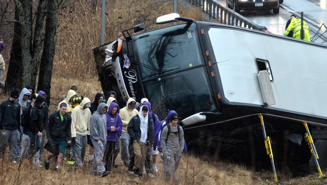 Members of the St. Michael's College lacrosse team walk away from the wrecked bus that was carrying them after it crashed  in Clifton Park, N.Y.