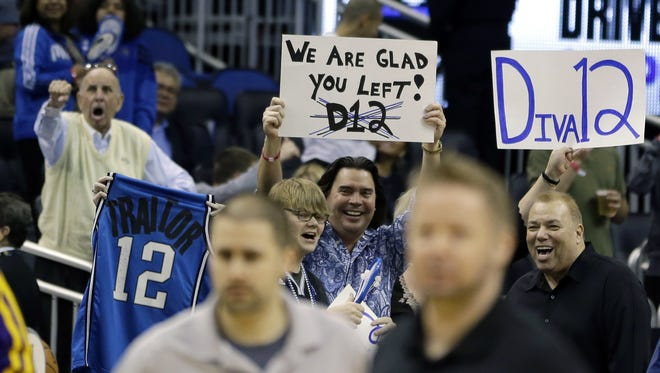 Orlando Magic fans hold up signs and shout at Los Angeles Lakers' Dwight Howard as he takes the court.