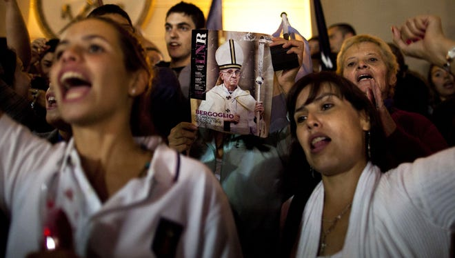 A worshiper holds up the front page of a magazine showing a photograph of new Pope Francis during Wednesday celebrations of his selection outside the Metropolitan Cathedral in Buenos Aires.