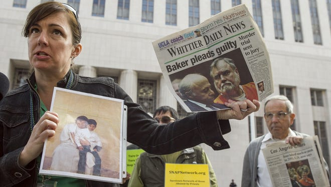 Survivor Joelle Casteix of Newport Beach, Calif., holds photos of defrocked priest Michael Baker outside the U.S. Attorney's office in Los Angeles. The Archdiocese of Los Angeles has announced a $10 million settlement with four Baker victims, raising their total to nearly $700 million in overall settlements to victims to date.