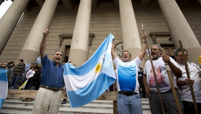 Faithful hold up an Argentine flag and sing Wednesday outside the Metropolitan Cathedral in Buenos Aires.
