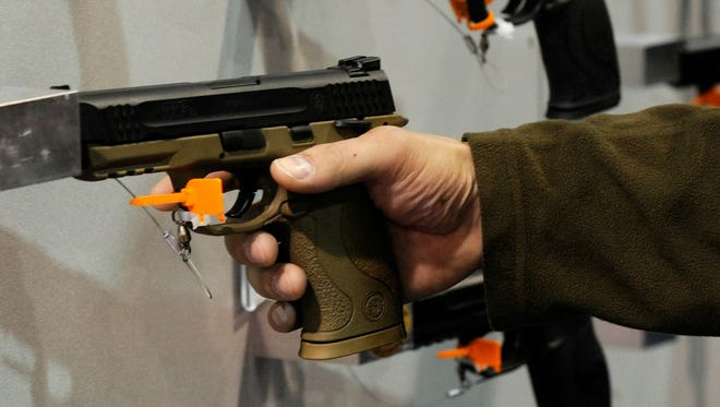 A convention attendee tries out  a handgun on display at the Smith & Wesson booth at the National Shooting Sports Foundation's  Shooting, Hunting and Outdoor Trade Show  in Las Vegas.