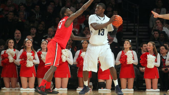 Villanova Wildcats forward Mouphtaou Yarou controls the ball against St. John's Red Storm forward JaKarr Sampson during the first half of a Big East tournament game at Madison Square Garden.