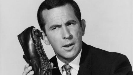 """Inept secret agent Maxwell Smart (Don Adams) from TV's """"Get Smart,"""" with the character's handy shoe phone, circa 1967. Max's go-to catchphrase? """"Missed it by THAT much!"""""""