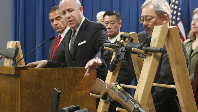 Senate President Pro Tem Darrell Steinberg, second from left,  points to a pair of semiautomatic rifles as he discusses a package of proposed  gun control legislation in Sacramento on Feb. 7, along with Sen. Leland Yee, D-San Francisco, third from left.