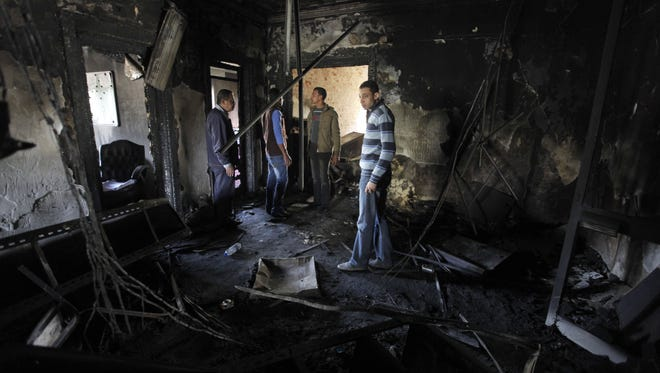 Egyptian workers walk amid the fire damaged headquarters of the Egyptian Soccer Federation in Cairo on Monday, two days after protesters set it on fire following a court verdict.