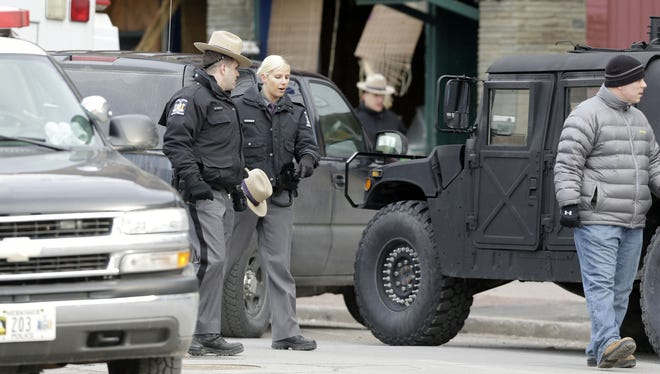Law enforcement officials work outside the building in Herkmimer, N.Y., where a man was killed after police stormed it following a standoff March 14. The man was suspected of killing four people the previous day.