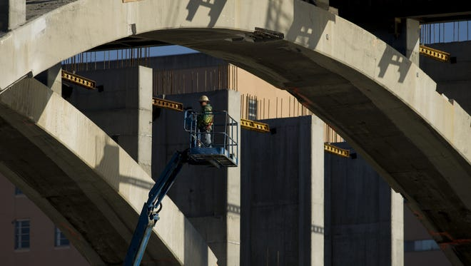 A construction worker rides a lift during a repair of the historic Henley Bridge in Knoxville, Tenn., on Jan. 3.