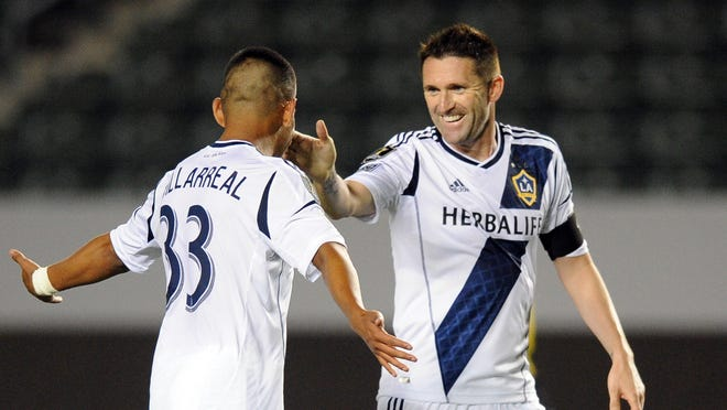 Los Angeles Galaxy forward Jose Villarreal (33) celebrates with Los Angeles Galaxy forward Robbie Keane (7) after scoring a goal against C.S. Herediano during the second half at the Home Depot Center on Wednesday. The Los Angeles Galaxy defeated C.S. Herediano 4-1.