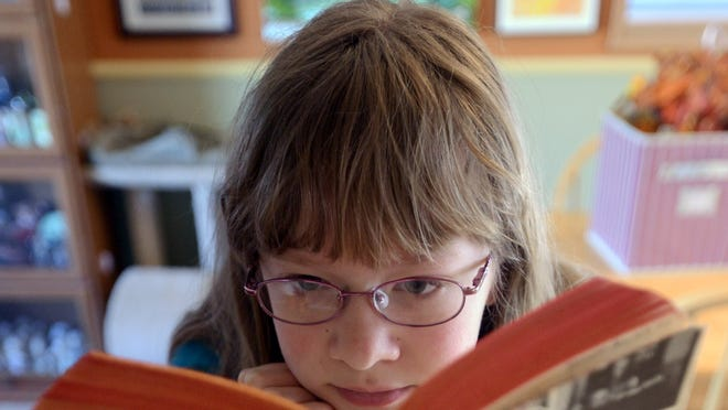 Home-schooled student Heather Mills of Loveland, a seventh grader, reads a book in her kitchen.