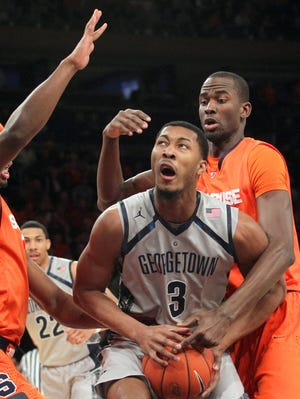 Georgetown forward Mikael Hopkins (3) is fouled by Syracuse Orange forward Baye Keita (12) in front of forward C.J. Fair (5) during the first half of a semifinal game of the Big East tournament at Madison Square Garden.