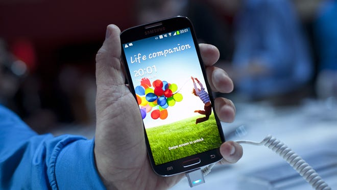 A Samsung employee displays the Samsung Galaxy S4 during an event in New York City.