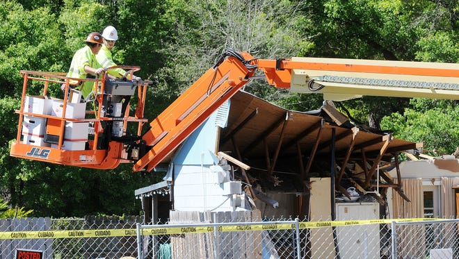 Workers remove belongings from the home where a sinkhole swallowed Jeffrey Bush on March 4, 2013, in Seffner, Florida.