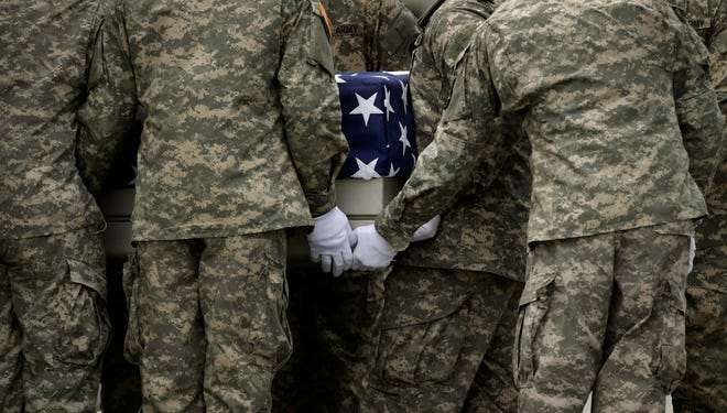 U.S. soldiers carry the flag-draped transfer case containing the remains of Army Spec. Jamal M. Rhett at Dover Air Force Base in Aug.  2010.