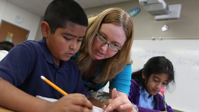 Third-grade teacher Jeni Bridges instructs student Leonardo Elorza while his classmate Judith Perez  works on an assignment at R.E. Good Elementary School in Carrollton, Texas, on Aug. 30.