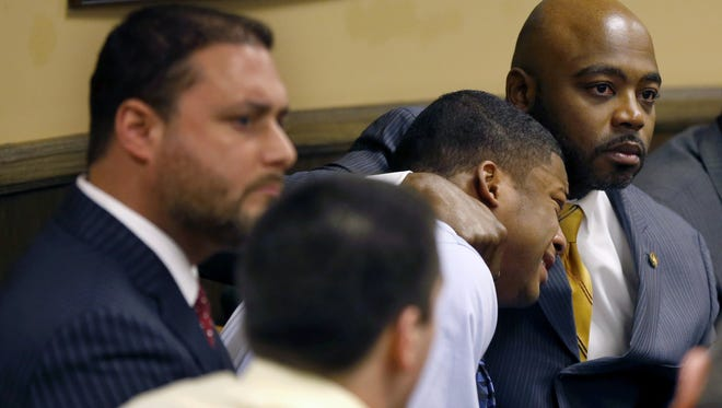 Defense attorney Walter Madison, right, holds his client, 16-year-old Ma'lik Richmond, second from right, while defense attorney Adam Nemann, left, sits with his client Trent Mays, foreground, 17, as Judge Thomas Lipps pronounces them both delinquent on rape and other charges after their trial in juvenile court in Steubenville, Ohio, on Sunday.