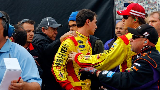 Joey Logano, center, gets held back by crew members after he tried to start an altercation with Denny Hamlin on pit road after Sunday's Food City 500 at Bristol Motor Speedway.