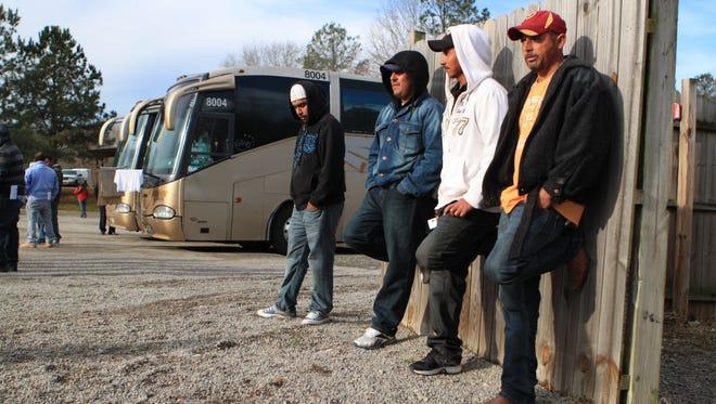From left to right, Alejandro Juarez Garcia, Noe Javier Belancourt Ortiz, Arnulfo Tinoco T., Jose Angel Rosas E., wait in the parking after having their visas processed.