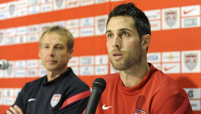 In this Feb. 28, 2012 file photo,?U.S. soccer team defender Carlos Bocanegra answers a question during a press conference prior to a training session ahead of their friendly  against Italy in Genoa. At left is coach Jurgen Klinsmann.