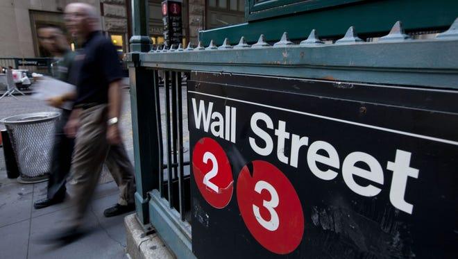 Pedestrians walk past a Wall Street sign near the New York Stock Exchange.