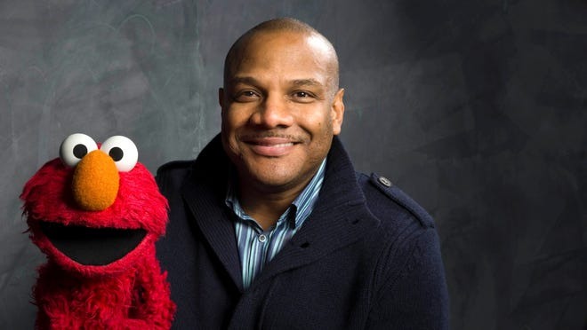 Former Elmo puppeteer Kevin Clash poses with the 'Sesame Street' muppet.