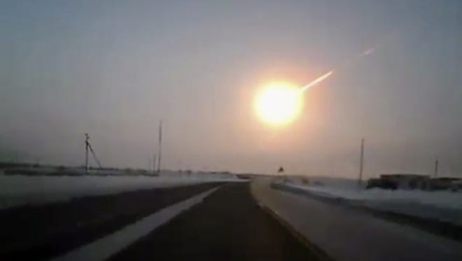 A meteor streaks across the sky in this frame grab made from a dashboard camera on a highway in Kostanai, Kazakhstan, on Feb. 15.