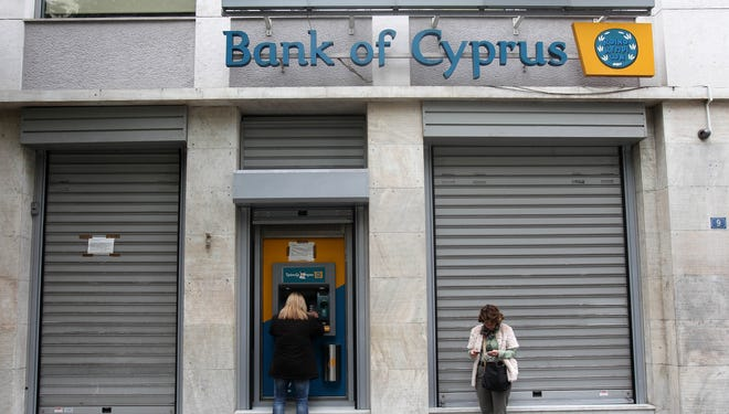 Customers of Bank of Cyprus use an ATM in Athens as the bank branch remains closed.