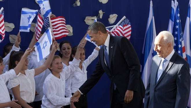 President Obama shakes hands with Israeli children as he is welcomed by Israeli President Shimon Peres in Jerusalem on Wednesday.