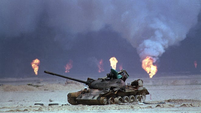 A destroyed Iraqi tank sits near oil well fires in northern Kuwait during the Gulf War in 1991. Gulf War illness has affected more than 250,000 veterans of the 1991 war against Iraq.