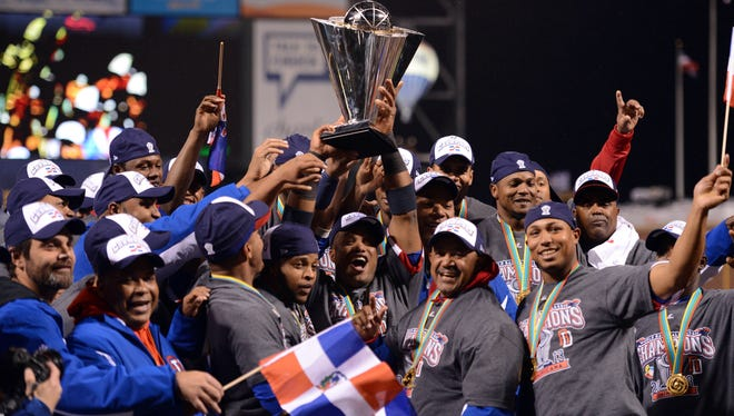 Dominican Republic second baseman Robinson Cano holds the World Baseball Classic championship after winning against Puerto Rico at AT&T Park.
