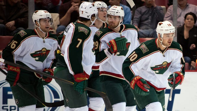 Minnesota Wild winger Devin Setoguchi is congratulated by teammates after scoring one of his two goals.