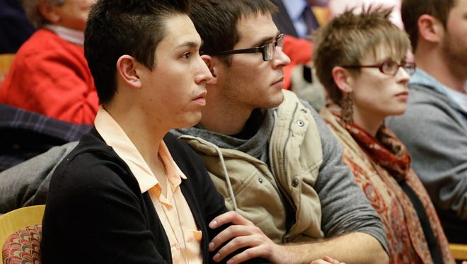 Marvin Garcia, left, and Kendall Rice hold hands as they listen to testimony on the civil unions bill in Denver on Jan. 23.